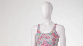 Floral tank top on mannequin. Colorful top and gray shorts. Cotton shorts with small belt. Bright pattern garment on display.