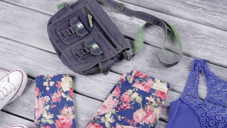 Floral trousers and blue top. Denim bag and canvas shoes. Girl's clothing on gray shelf. Sense of style.