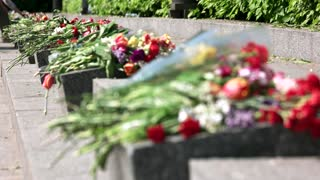 Flower bouquets on memorial granit stones. Close up. Memorial day.