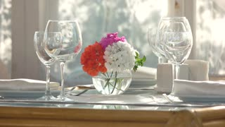 Flower vase on dining table. Side view of shiny wineglasses. Cafe decoration ideas.