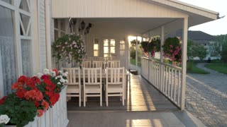 Flowers hanging on a porch. White colored house and sunlight. Time to come back home.