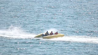 Flying banana boat, jet ski. People and sparkling sea.