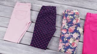 Folded pants of different color. Dark navy and pink trousers. Special prices for new items. Quality goods on store showcase.