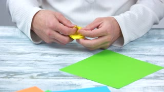 Folding paper, creating origami figure. First step of making yellow origami flower, close up.