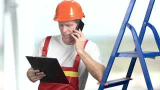 Foreman with clipboard and phone. Construction engineer leaning on ladder and talking on mobile phone, blurred background.