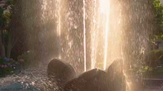 Fountain in slow-mo. Splashes of water and sunlight. Life of nature.