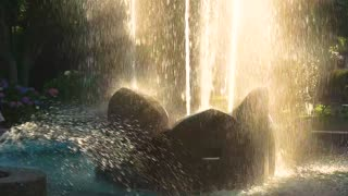 Fountain in the park, slow-mo. Water splashes and sunlight.