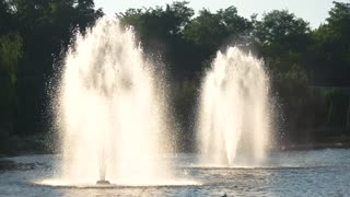 Fountains spraying water outdoor. Pond and trees.
