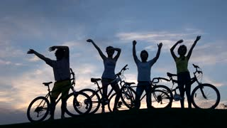 Four cheerful cyclists dancing at sunset sky. Four yung friends with bikes having fun on evening nature background.