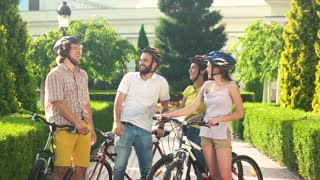 Four cyclists laughing outdoors, slow motion. Group of young cheerful friends having fun in park, sunny day. Active summer leisure.