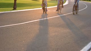 Four friends cycling on the road. Sporty company of friends on bicycles outdoors, sunny day. Group of young people riding bicycles.