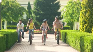Four happy cyclists enjoying riding bicycles. Cheerful group of friends riding bikes in park, slow motion. Time spending with best friends is priceless.