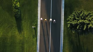 Four persons riding bikes, aerial view. Group of cyclists riding bicycles along a road, shooting from a height with a drone. Best friends and road ahead.