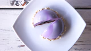 French mousse with strawberry and white chocolate. Mirror glazed blueberry mousse dome, top view. Morning at the bakery.