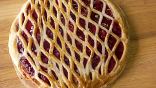 Freshly baked pie with cherry. Pastry on wooden board. Delicious dessert from natural ingredients.