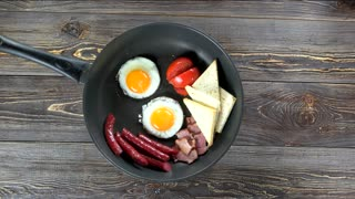 Fried eggs, bacon and toasts. Tasty food on the table.