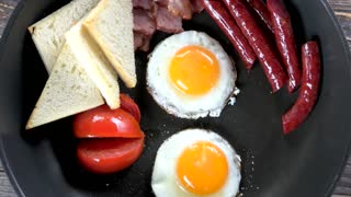 Fried eggs, sausages and tomato. Traditional English breakfast.