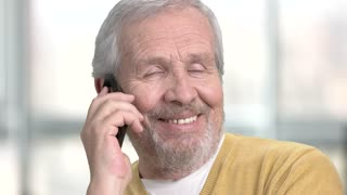 Friendly caucasian pensioner talking on phone. Close up senior european man with mobile phone on blurred background.