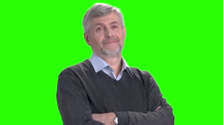 Friendly mature man with arms crossed. Thoughtful middle-aged man standing with arms folded and nodding with head on Alpha Channel background.
