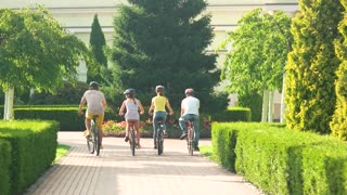 Friends doing bike ride outdoors. Four cheerful friends in riding bicycles in park. Beautiful weekend with friends.
