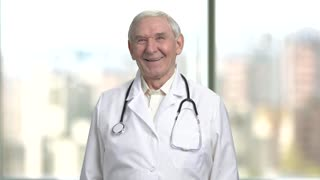 Front view cheerful senior doctor laughing hard. Portrait of a jovial old male doctor in lab coat and stethoscope. Bright abstracrt blurred windows background with view on city.