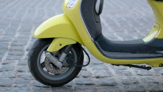 Front wheel of a scooter. Legs of man in shoes. Transport with low fuel consumption. Start the engine.