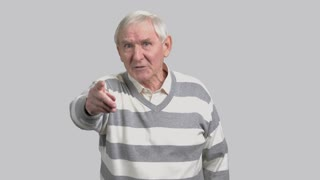 Frustrated aged man on grey background. Angry senior person arguing and gesturing with index finger. Pensioner fight for his rights.