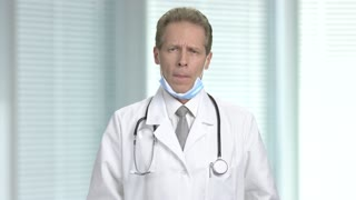 Frustrated male doctor on blurred background. Depressed mature caucasian doctor. How to deliver bad news.
