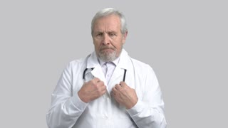 Frustrated senior doctor on gray background. Unhappy older medical worker, portait. Concept of problems and failure.