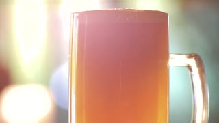 Full glass of thick orange beer. Glass full of turbid ale, head close up.