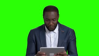 Funny afro american businessman playing on pc tablet. Cheerful african american guy in formal wear playing on computer tablet on green screen.