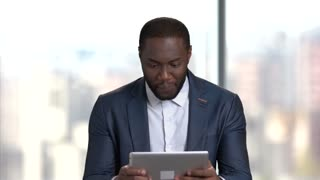 Funny dark-skinned businessman playing online game. Afro-american man in business suit playing game on pc tablet. Break at work.