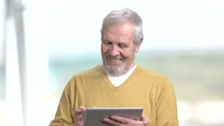 Funny elderly man with pc tablet. Happy smiling grandpa using digital tablet on blurred background. Senior people and modern technology.