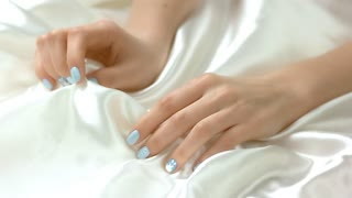 Gentle manicure and white silk fabric. Young woman hands with beautiful blue manicure and delicate silk material. Female tenderness and care.