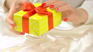 Gift box in beautiful hands, slow motion. Young woman hands with romantic nail design holding box with present tied with red ribbon. Saint Valentine Day celebration.
