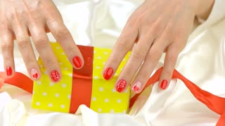 Gift box unpacking, slow motion. Young woman hands with red festive manicure opening yellow gift box on white silk. Romantic holiday concept.