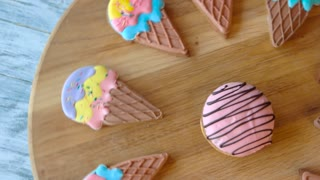 Gingerbread sweets on round wooden board. Biscuits with frosting. Confectionery for kids.