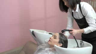 Girl getting her hair washed. Female beautician at work.