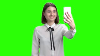 Girl having online video coversation on smartphone. Emotional positive cute woman. Green screen hromakey background for keying.