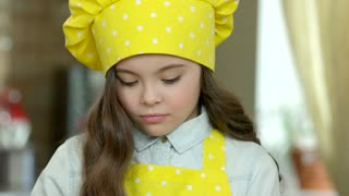 Girl in chef hat. Child cooking food.