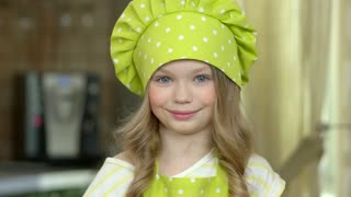 Girl in chef hat smiling. Child is cooking.