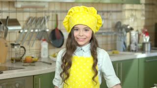 Girl in chef uniform smiling. Happy child on kitchen background.