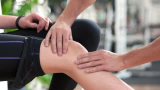 Girl injured her leg during gym training. Male hands doing a massage to female knee at gym close up. Training accident concept.