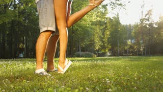Girl kissing a guy. Close-up legs of guy and girl. Lovers embrace. Love story in the park.
