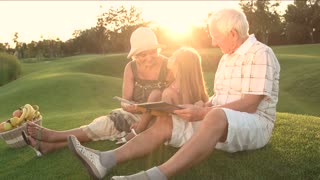 Girl kissing grandmother outdoors. Grandparents and granddaughter sitting outdoors with photo album. Happy family on picnic.