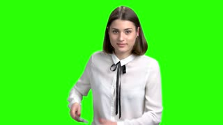 Girl pulls the phone out from her back pocket. Portrait of young brunette woman. Green screen hromakey background for keying.