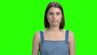 Girl shows silence gesture. Young woman with finger in front of her mouth. Shut up gesture, green screen hromakey background for keying.