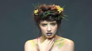 Girl wearing nature themed makeup. Beautiful woman touching her face.