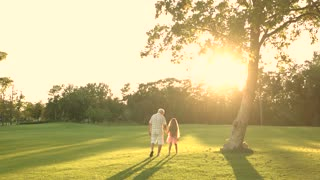 Girl with grandfather walking outdoors. Park, sun and people. Beautiful summer walk.