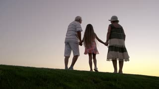 Girl with grandparents at sunset. Slow motion senior man and woman with granddaughter on evening sky background. Enjoying the infinity.
